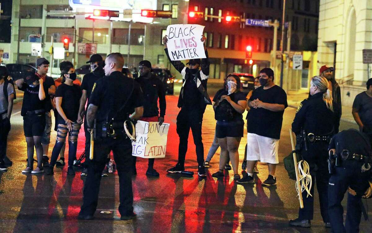 Demonstrators remain near an entrance to Alamo Plaza as the curfew time for downtown approaches on the day after the downtown riots on May 31, 2020.
