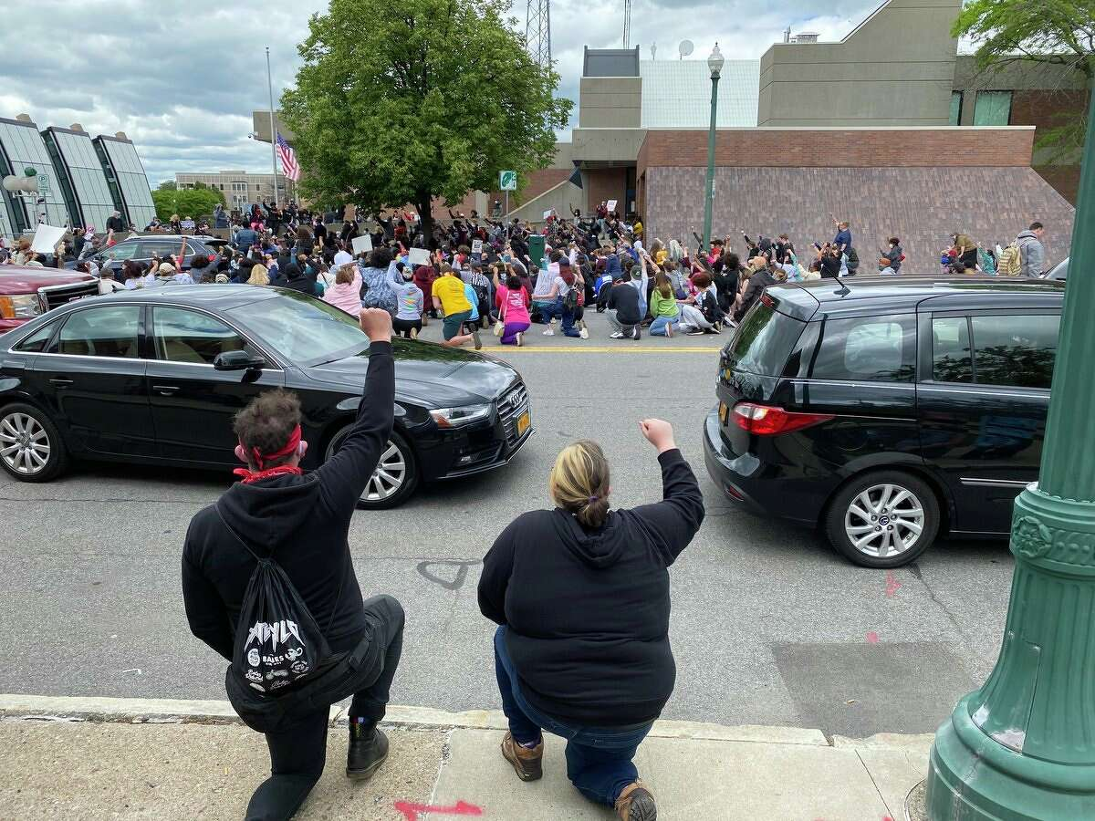 Protesters take a knee outside Schenectady police headquarters at a rally Sunday afternoon against police brutality.