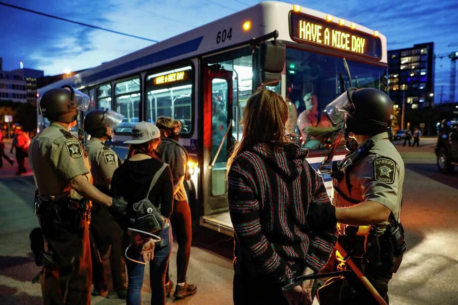 Arrested protesters are loaded onto a transport bus by police on South Washington Street, Sunday, May 31, 2020, in Minneapolis. Protests continued following the death of George Floyd, who died after being restrained by Minneapolis police officers on Memorial Day. Photo: John Minchillo, AP / Copyright 2020 The Associated Press. All rights reserved.