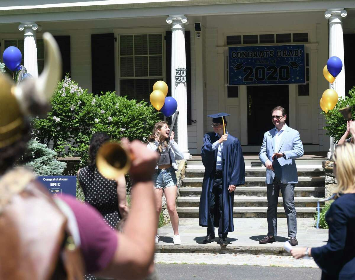 New graduate Eric Degter moves his tassel from one side to the other while his family celebrates as members of King School faculty perform a drive-thru commencement at his home in Stamford on Sunday.