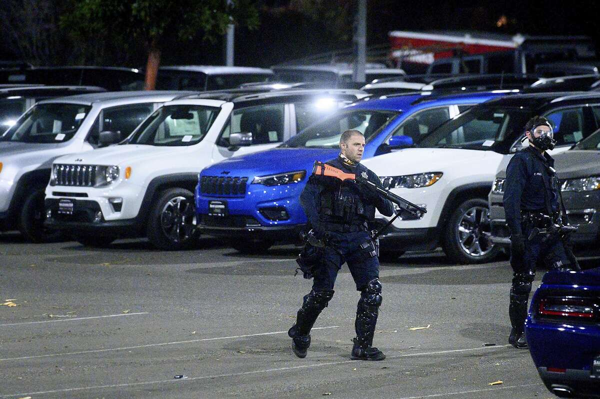 A police officer searches a San Leandro, Calif., car dealership shortly after multiple vehicles we stolen on Monday, June 1, 2020. Widespread looting left dozens of businesses vandalized throughout San Leandro and surrounding cities as protests against the death of George Floyd who died in Minneapolis police custody on May 25, 2020.