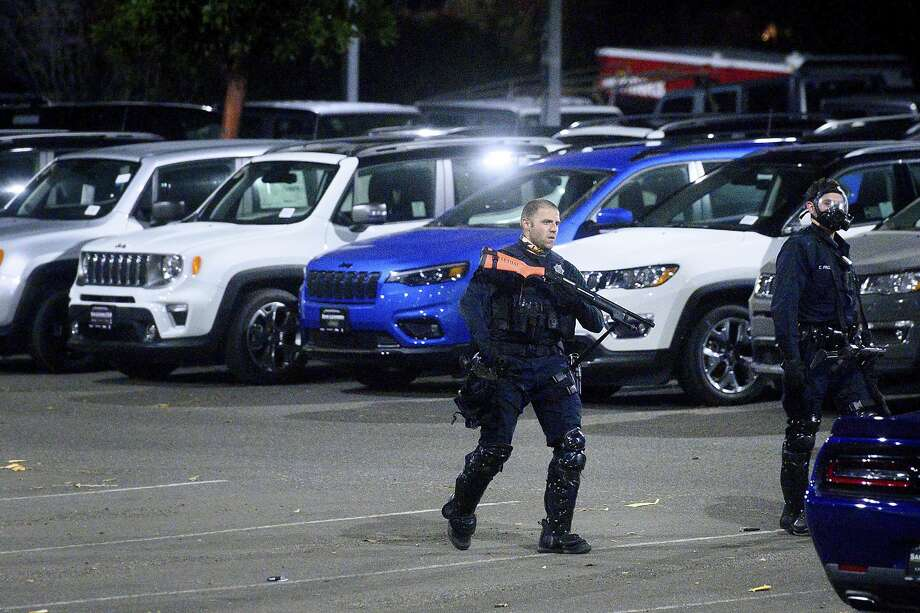 A police officer searches a San Leandro, Calif., car dealership shortly after multiple vehicles we stolen on Monday, June 1, 2020. Widespread looting left dozens of businesses vandalized throughout San Leandro and surrounding cities as protests against the death of George Floyd who died in Minneapolis police custody on May 25, 2020. Photo: Noah Berger/Associated Press