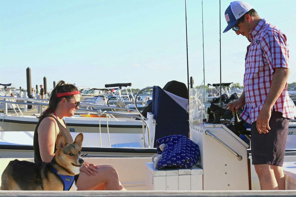 Jacey and Chris Davies of Westport hang out on their boat with their dog Chester at the E.R. Strait Marina on Saturday, May 30, 2020, in Westport, Conn.