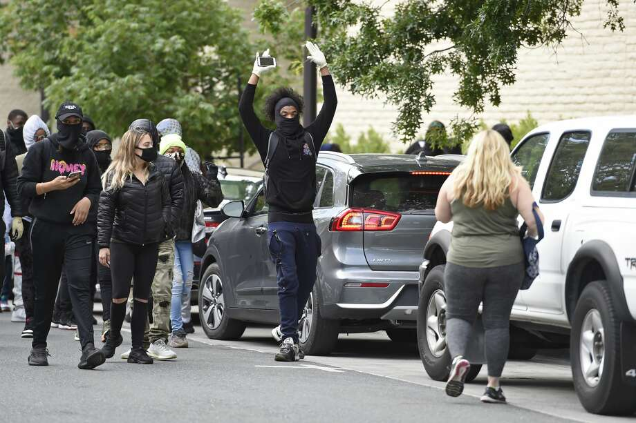 A shopper tries to get into her vehicle as protesters march down Broadway in downtown Walnut Creek, Calif., on Sunday, May 31, 2020. People are protesting all over the country because of George Floyd's death by a Minneapolis police officer. Photo: Bay Area News Group, Jose Carlos Fajardo/Associated Press / @BAY AREA NEWS GROUP 2020