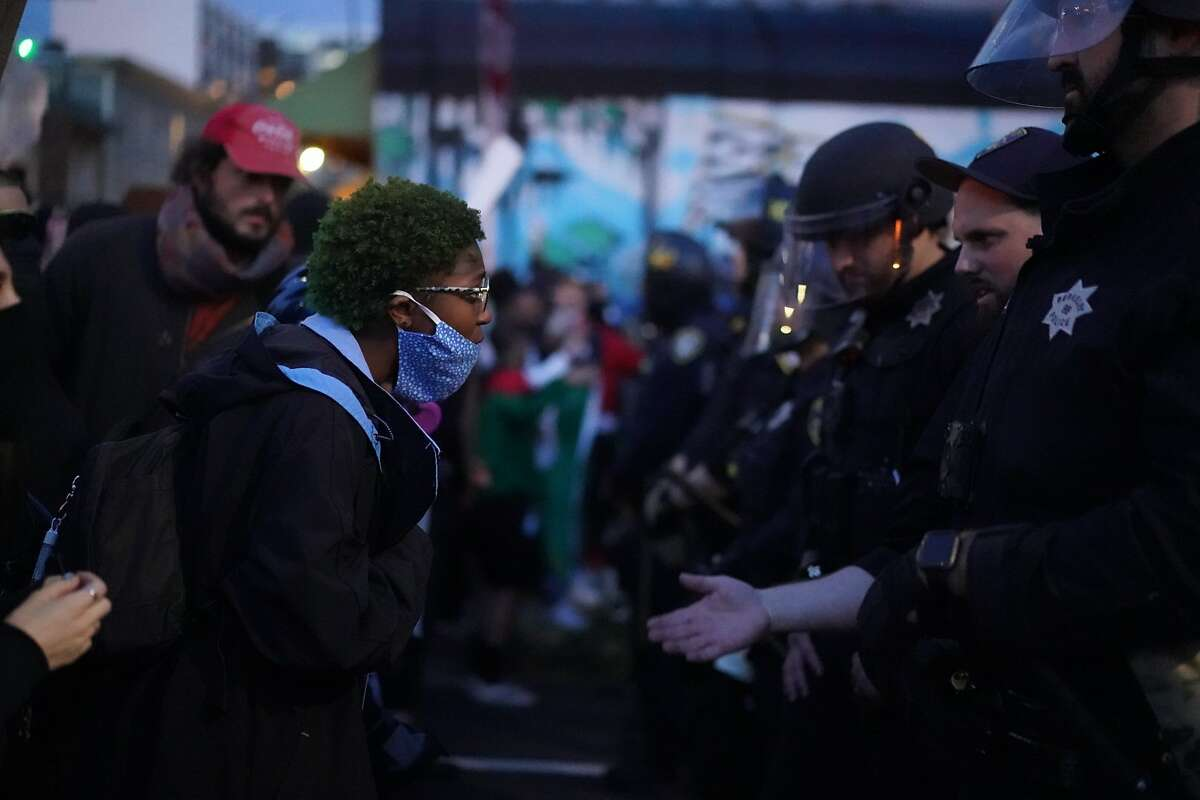 People confront a line of Oakland police officers at 8th and Clay streets Sunday during a protest spurred by the death of George Floyd in Minneapolis a week earlier.Photo: Paul Kuroda / Special to The Chronicle