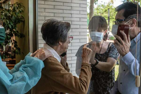 ESPLUGUES DEL LLOBREGAT, SPAIN - MAY 19: Carme Peris, 88 tries to touch the hand of her granddaughter Mar as she speaks on the phone with her son Francesc during a visit through a window at La Mallola nursing home on May 19, 2020 in Esplugues del Llobregat, near Barcelona, Spain. As measures ease in Spain, nursing homes remains still locked down to protect elderly people and prevent new outbreaks. La Mallola nursing home has started a program of visits for relatives of residents using one of their big windows. Many of the hundreds of thousand of residents in Spain's nursing homes are already at risk for loneliness, which research shows can undermine their physical and mental health due to the strict quarantine measure to fight the novel coronavirus. This program aims to improve the lockdown of elderly people living in this nursing home as they approach their third month without visits of their close relatives. Over 18,000 elderly people in nursing homes have died in Spain due to COVID-19 pandemic. (Photo by David Ramos/Getty Images)