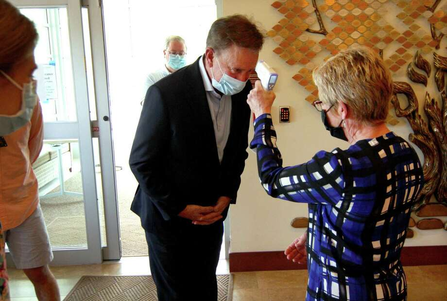 Governor Ned Lamont gets his temperature checked after arriving for a visit to The Jewish Home senior services facility on Park Ave in Bridgeport on May 15. Photo: Christian Abraham / Hearst Connecticut Media / Connecticut Post