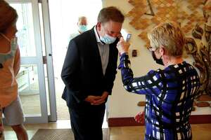 Governor Ned Lamont gets his temperature checked after arriving for a visit to The Jewish Home senior services facility on Park Ave in Bridgeport on May 15.