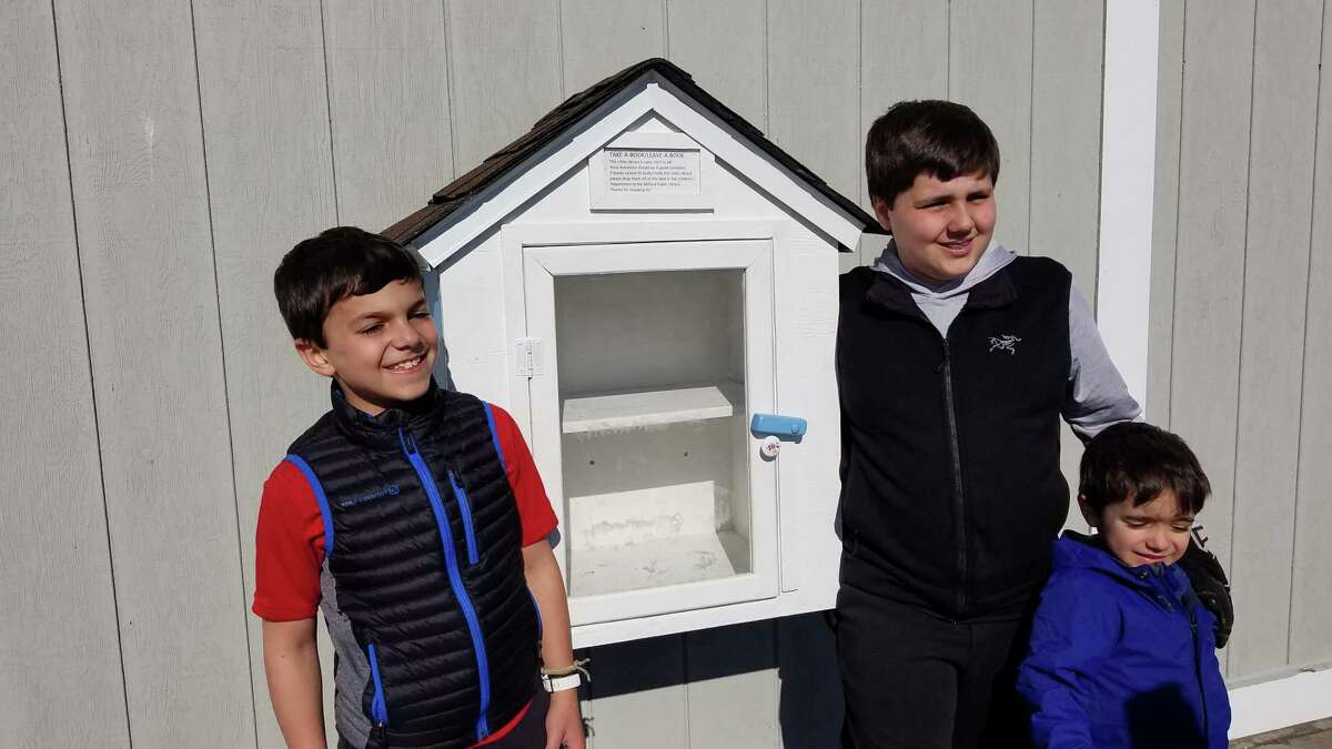 Pat Simon's grandsons, Tristan, Julian and Adrian stand next to the finished little library they helped to rebuild.