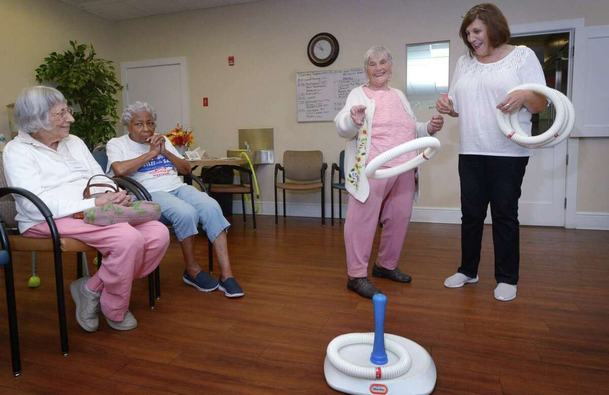 Clients of the Elderhouse day care center in Norwalk participate in activity time with the help of an employee.
