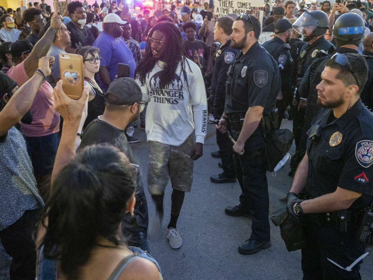 As the night went on different activists offered words of encouragement 05/31/2020 to the crowd gathered outside Midland Park Mall. Jaime Moreno is seen in the foreground wearing a black shirt and black hat.