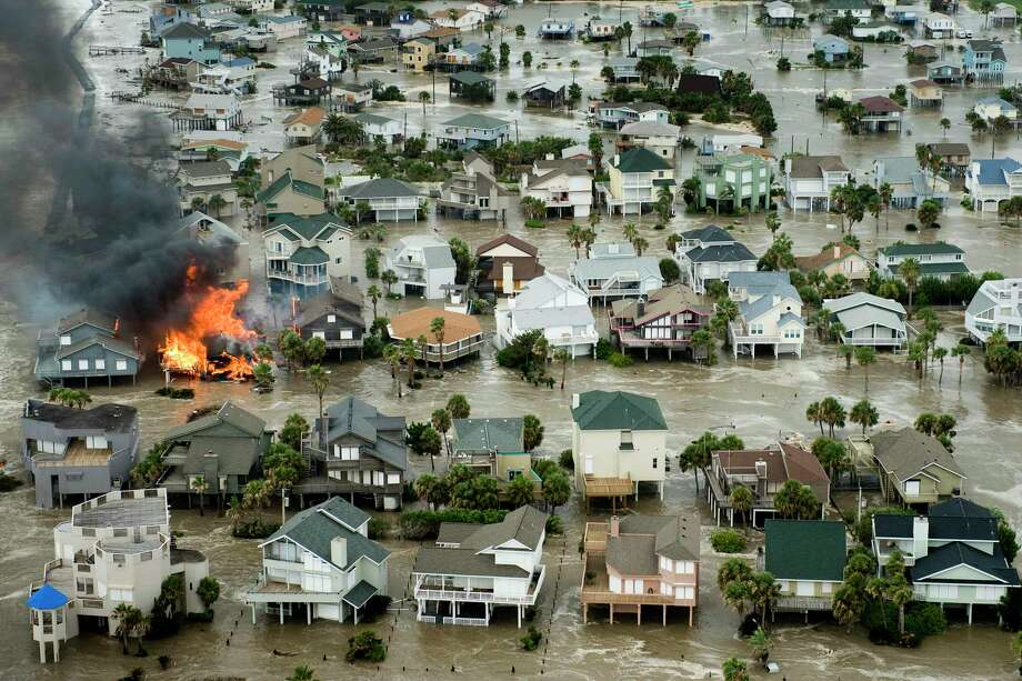 A house is totally engulfed in flames as floodwaters and crashing waves inundated beach homes on Galveston Island as Hurricane Ike approaches the Texas Gulf Coast, Friday, Sept. 12, 2008. ( Smiley N. Pool / Chronicle ) Photo: Smiley N. Pool, Staff / Houston Chronicle / Houston Chronicle