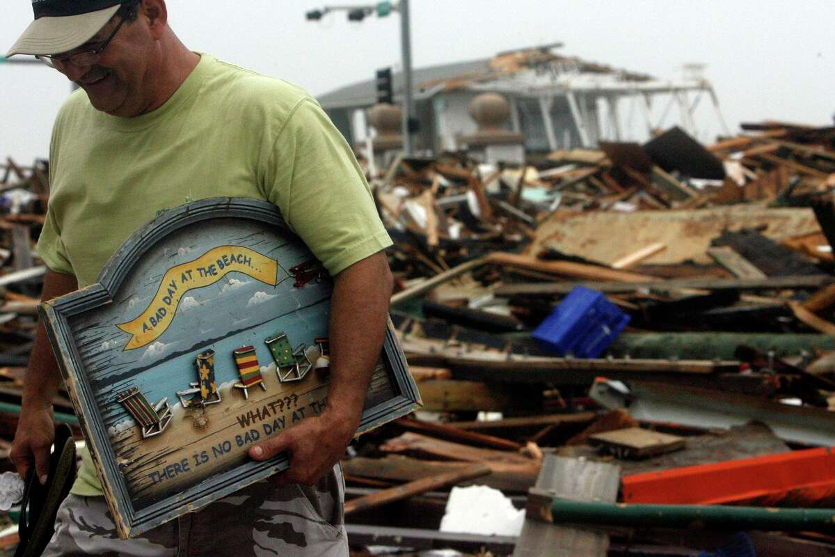 """Galveston residents Henry Vasquez grabs a souvenir from the rubble of Murdock's Pier and Hooters left by Hurricane Ike that reads """"A bad day at the beach. What??? There's no bad day at the beach."""" Seawall Blvd. Saturday, Sept. 13, 2008. """"I can't believe this,"""" Vasquez said. """"It's unreal."""" ( Johnny Hanson / Chronicle )"""