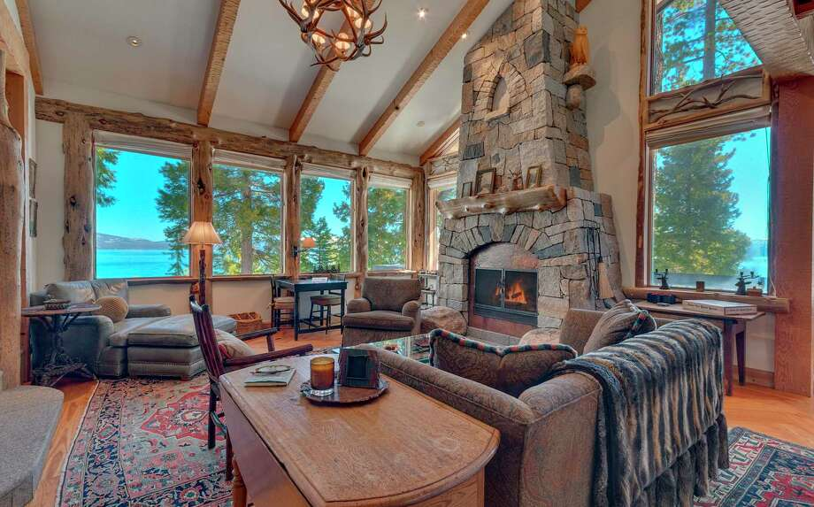 The living room of 6400 West Lake Blvd. in Lake Tahoe's Chambers Landing features views of the water through wood-framed windows, while a stone fireplace stretches from floor to ceiling. Photo: Sierra Sotheby's International Realty