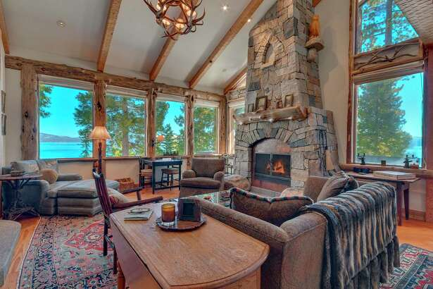The living room of 6400 West Lake Blvd. in Lake Tahoe's Chambers Landing features views of the water through wood-framed windows, while a stone fireplace stretches from floor to ceiling.