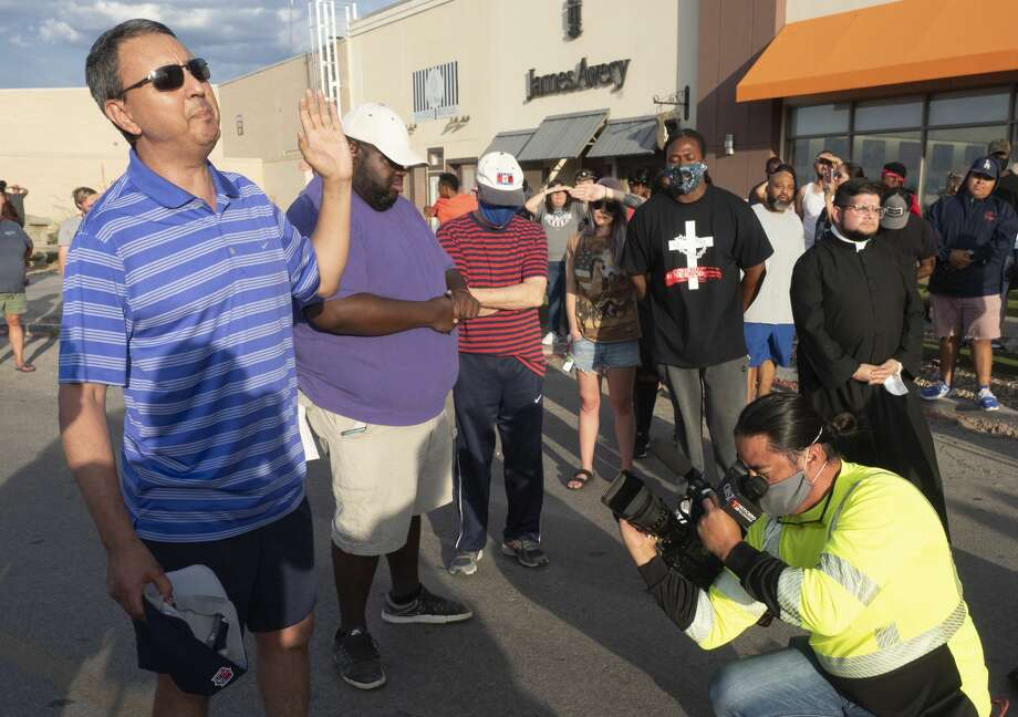 Pastors from across faiths come together to pray over the protesters gathered outside Midland Park Mall. Rev. Freddy Perez of St. Stephen's Catholic Church is seen in the far right. Photo: Tim Fischer/Midland Reporter-Telegram