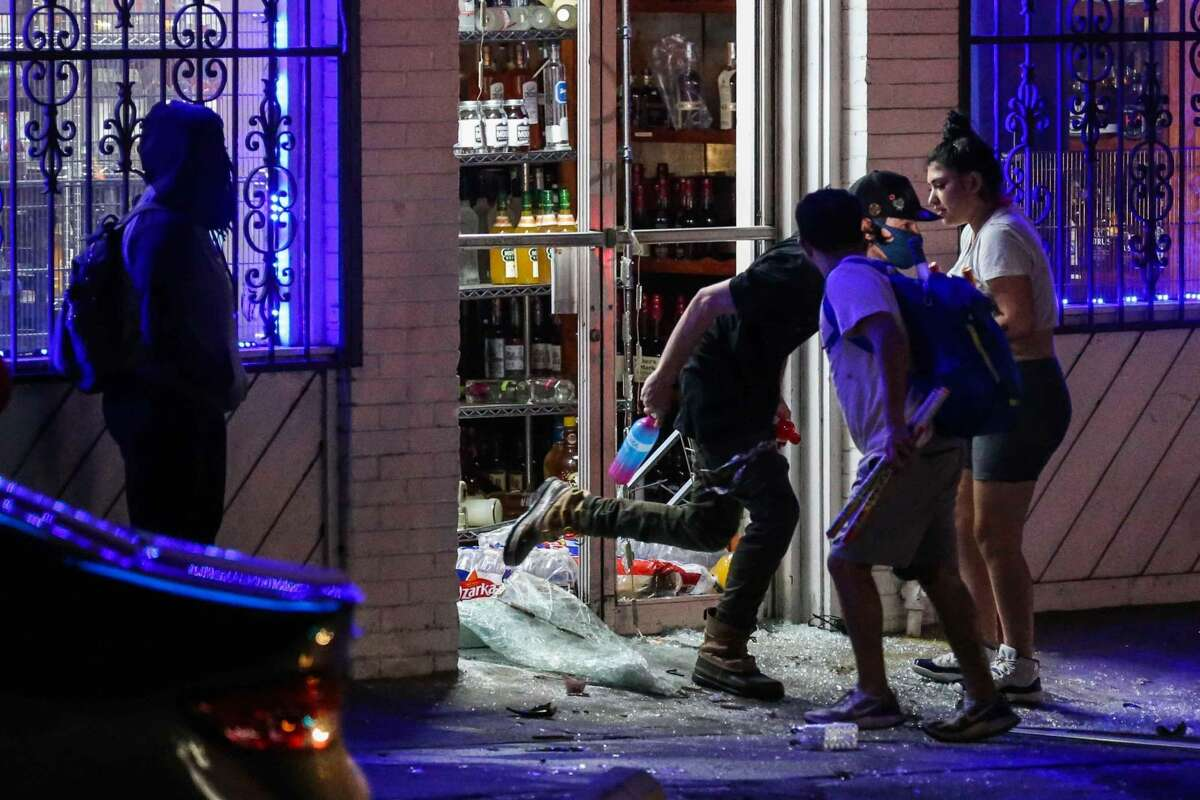 A liquor store at E. Sixth Street and Interstate 35 is looted during a protest in downtown Austin early Monday. (Lola Gomez/Austin American-Statesman)