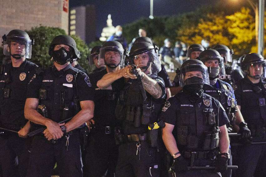 Austin police in riot gear face off with protesters early Saturday. {Dave Creaney for American-Statesman]