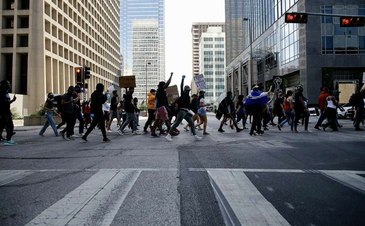 People walk the streets as they march In downtown Dallas, on Sunday, May 31, 2020. George Floyd died in police custody in Minneapolis on May 25. Minneapolis police officer Derek Chauvin, who had his knee on the neck of Floyd for at least five minutes, has been charged with murder and manslaughter. (Vernon Bryant/The Dallas Morning News/TNS)