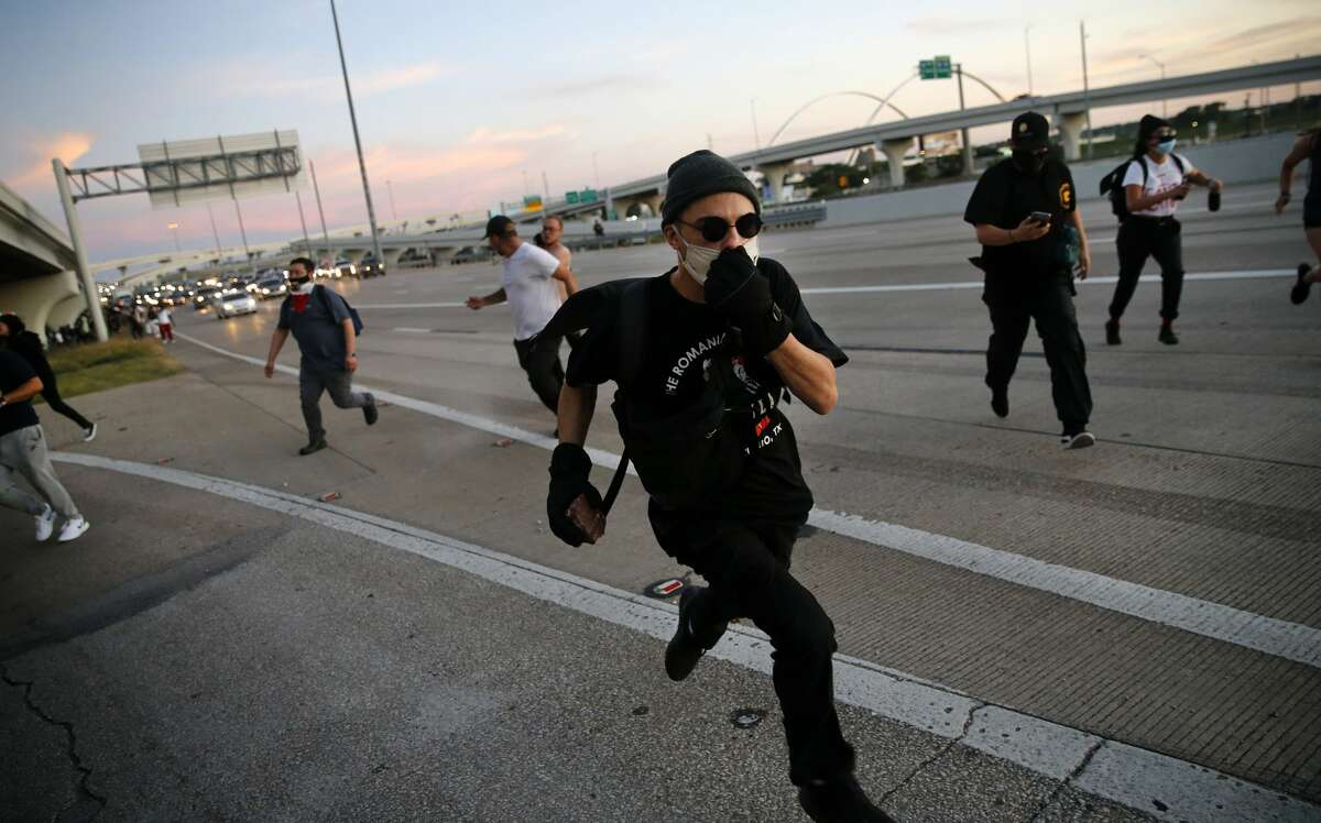 Protestors race away from arresting Dallas police officers after shutting down northbound Interstate 35. Police fired projectiles at them, forcing them off the interstate. They gathered to protest the in-custody death of George Floyd in downtown Dallas, Saturday, May 30 2020. (Tom Fox/The Dallas Morning News/TNS)