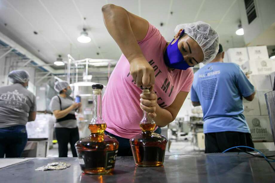 Angie Medina corks a bottle at Gulf Coast Distillers in Houston, TX, on May 29, 2020. Photo: Annie Mulligan, Houston Chronicle / Contributor / © 2020 Annie Mulligan / Houston Chronicle