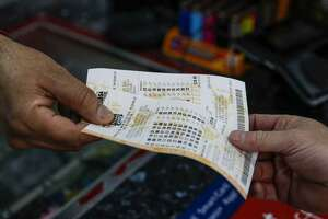 A cashier hands lottery tickets to a customer.