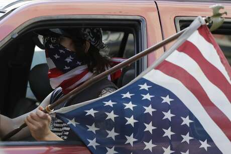 A person holds an American flag as he drives on the street during a protest over the death of George Floyd in Chicago, Saturday, May 30, 2020.Protests across the country have escalated over the death of George Floyd who died after being restrained by Minneapolis police officers on Memorial Day, May 25. (AP Photo/Nam Y. Huh)