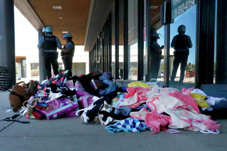 Chicago police officers stand outside a clothing store in the Bronzeville neighborhood after it was broken in to and merchandise taken. Charles Rex Arbogast   AP