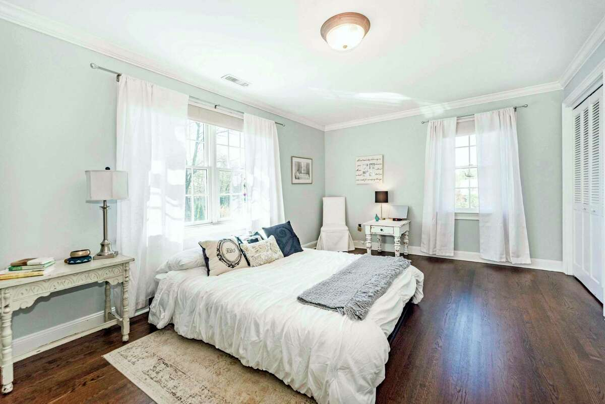 The master bedroom suite features two walk-in closets with built-in dresser drawers, a ceiling fan, and a luxurious private bath.