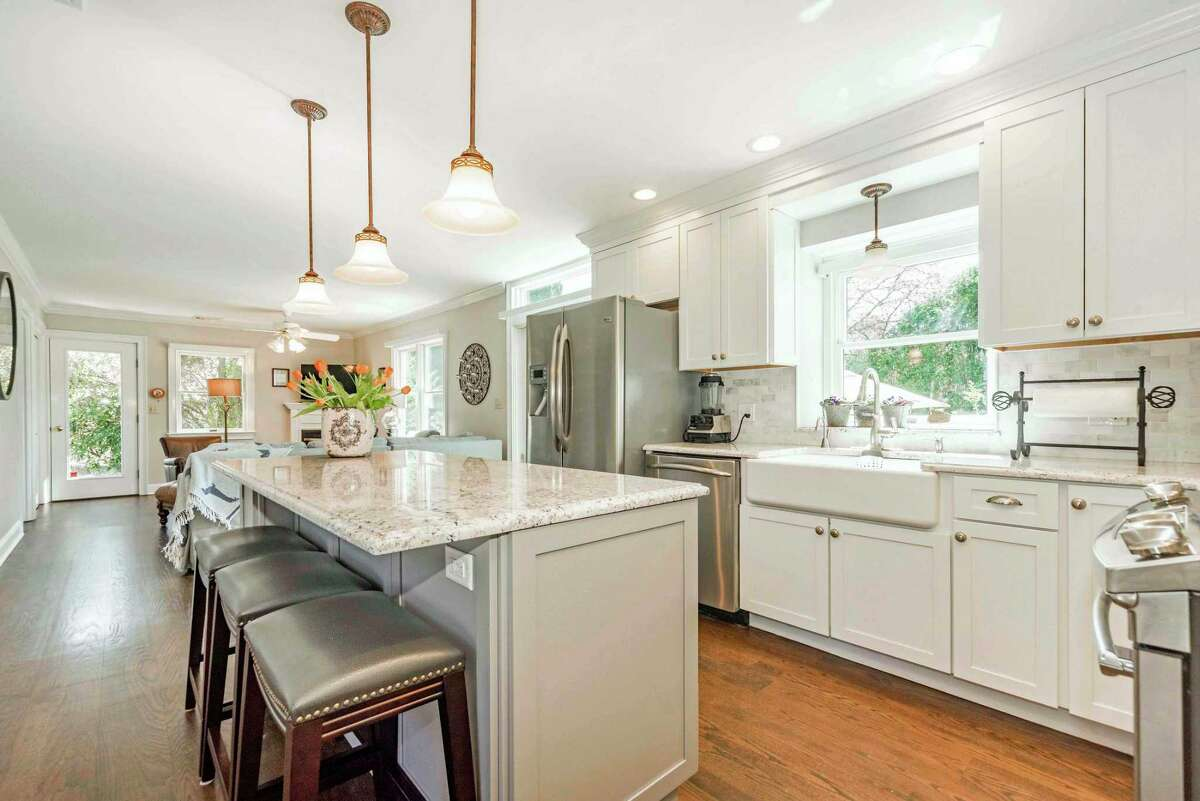 The updated gourmet kitchen features a center island with a breakfast bar for three, ogee-edged granite counters, a large farm sink, and high-end appliances.