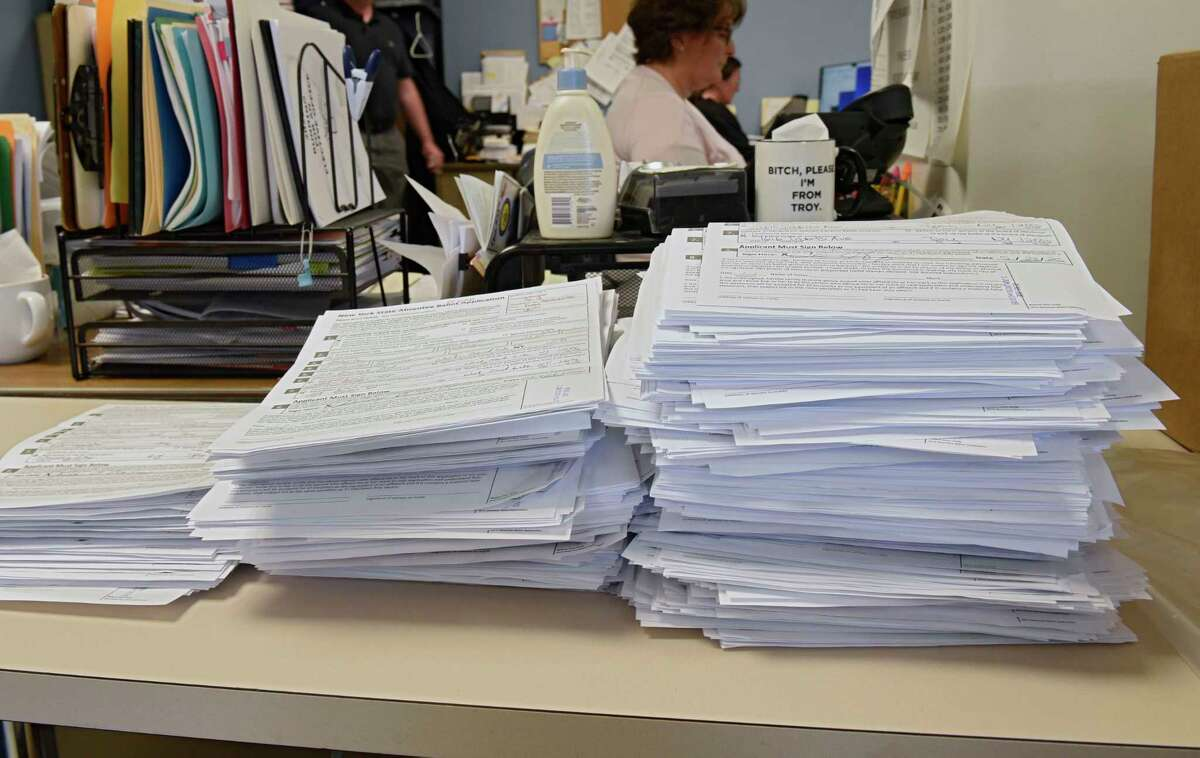 Filled out applications for absentee ballots are seen stacked on a desk as Rensselaer County Board of Elections handles thousands of absentee ballots for June 23 primary on Monday, June 1, 2020 in Troy, N.Y. School districts must also send out ballots for their budget and school board elections by June 3. But a snafu has made the envelopes to send them in scarse. (Lori Van Buren/Times Union)