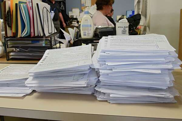 Filled out applications for absentee ballots are seen stacked on a desk as Rensselaer County Board of Elections handles thousands of absentee ballots for June 23 primary on Monday, June 1, 2020 in Troy, N.Y. (Lori Van Buren/Times Union)