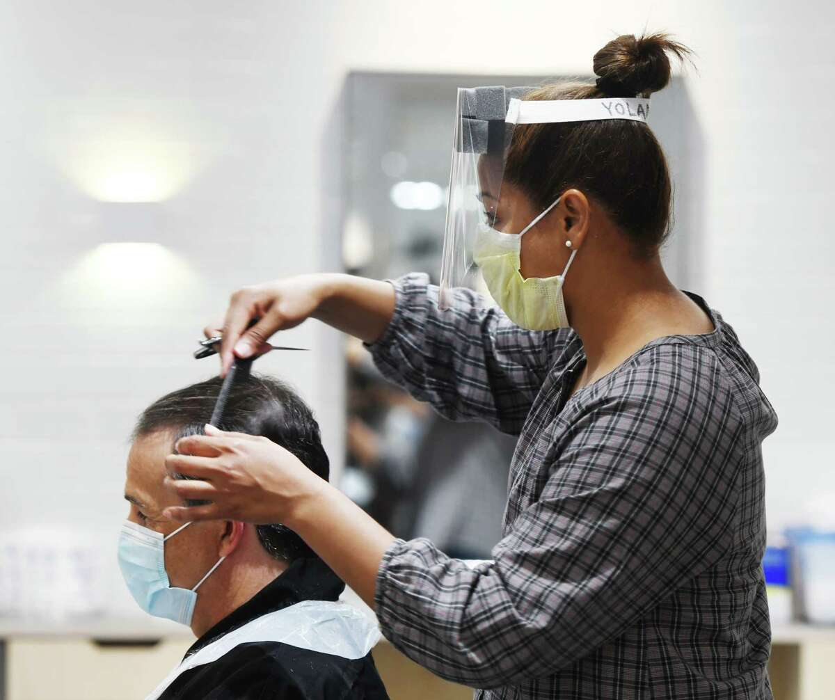 Yolanda Ortiz gives a haircut at Hopscotch Salon in Old Greenwich, Conn. Monday, June 1, 2020. Barbershops, hair salons, and casinos in Connecticut were allowed to reopen with restrictions on Monday.