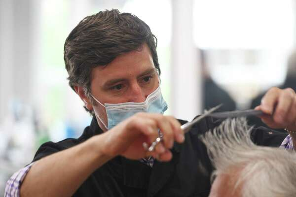 Antonio Merolla gives a haircut to a client at Classic Barber of Greenwich in Greenwich, Conn. Monday, June 1, 2020. Barbershops, hair salons, and casinos in Connecticut were allowed to reopen with restrictions on Monday.