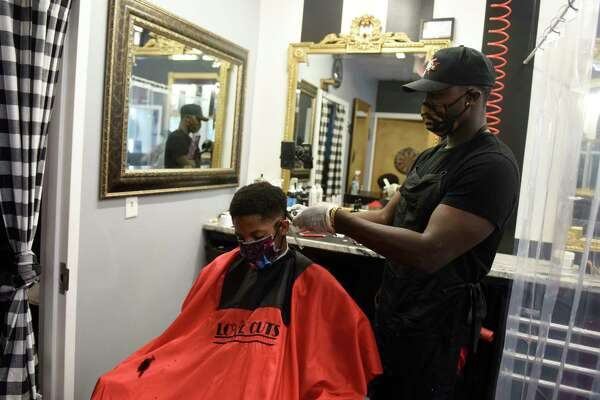 Jeremiah Jean Louis gets his hair cut by Malcolm Green on the first day of reopening at Love Cuts in Stamford, Conn. Monday, June 1, 2020. Barbershops, hair salons, and casinos in Connecticut were allowed to reopen with restrictions on Monday.