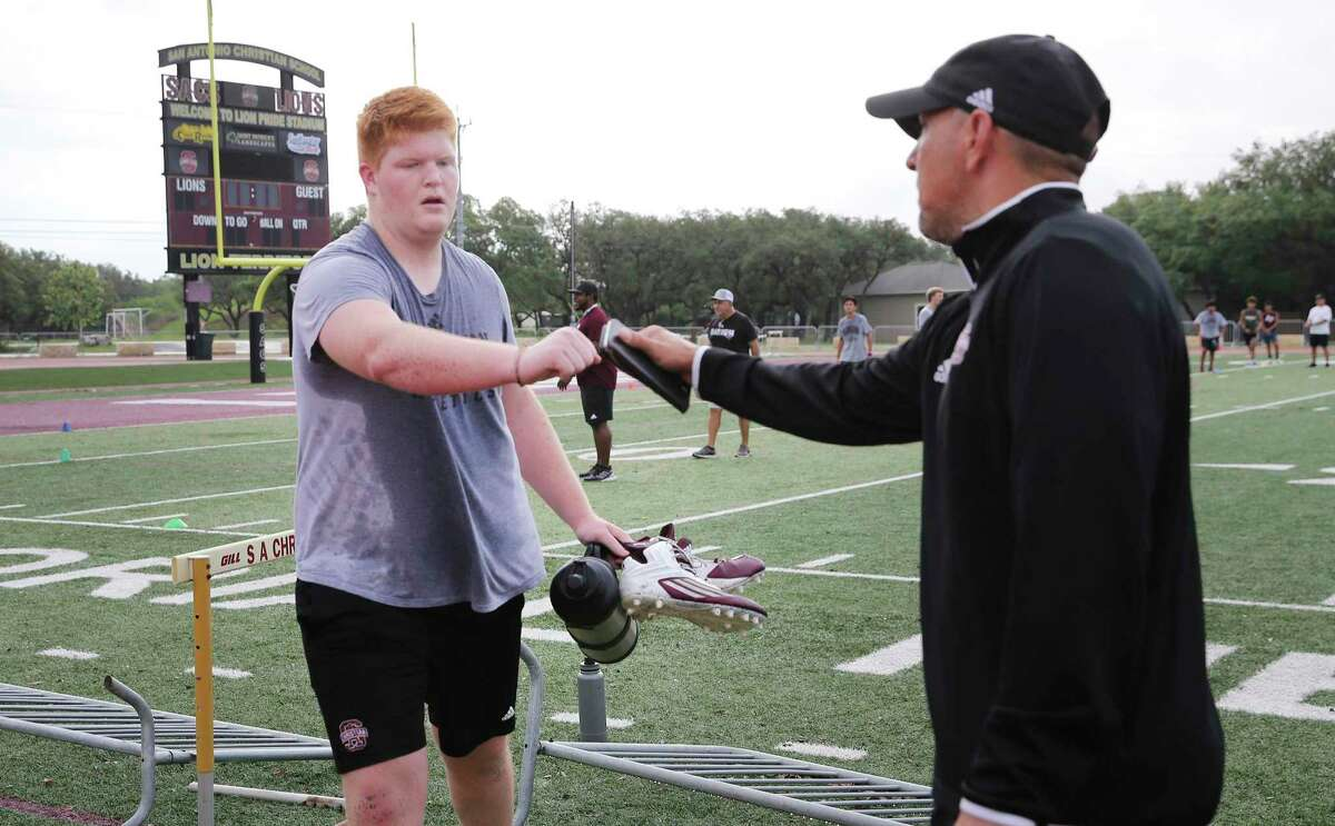 Brandon Parrott (right), San Antonio Christian athletic director, gets a fist bump from junior Ethan Sanders during the first day of summer conditioning camps on Monday.
