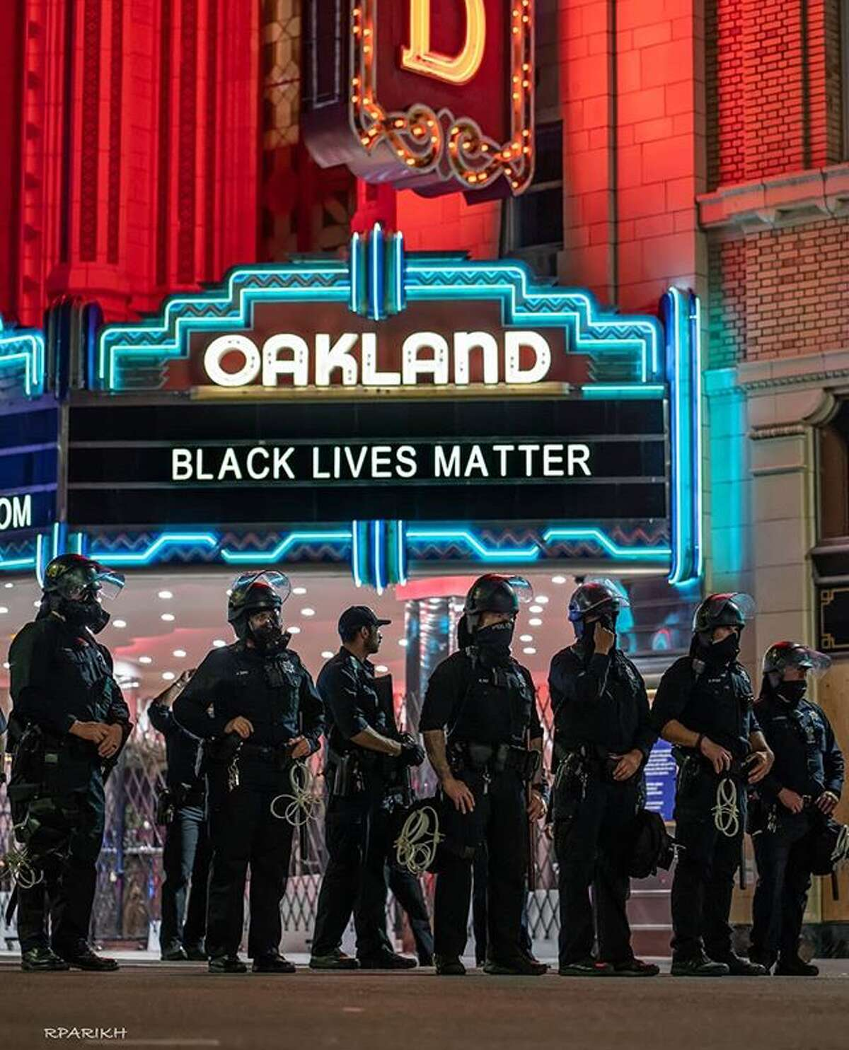 Police officers stand outside the Fox Theater in Oakland during a night of protests after the death of George Floyd. (@rinarage)