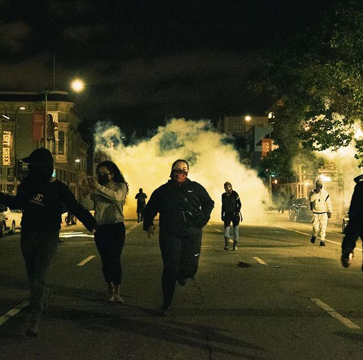 Protesters run from tear gas in Oakland. (@itsnickmar)