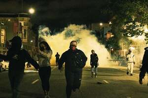 Protesters run from tear gas in Oakland, California. ( @itsnickmar )