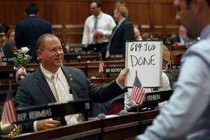 State Rep. Craig Fishbein, R-Wallingford, holds up a sign after a vote during the final day of session at the State Capitol in Hartford, Conn., Wednesday June 5, 2019. (AP Photo/Jessica Hill)