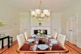In the formal dining room there is a marble fireplace and chair railing.