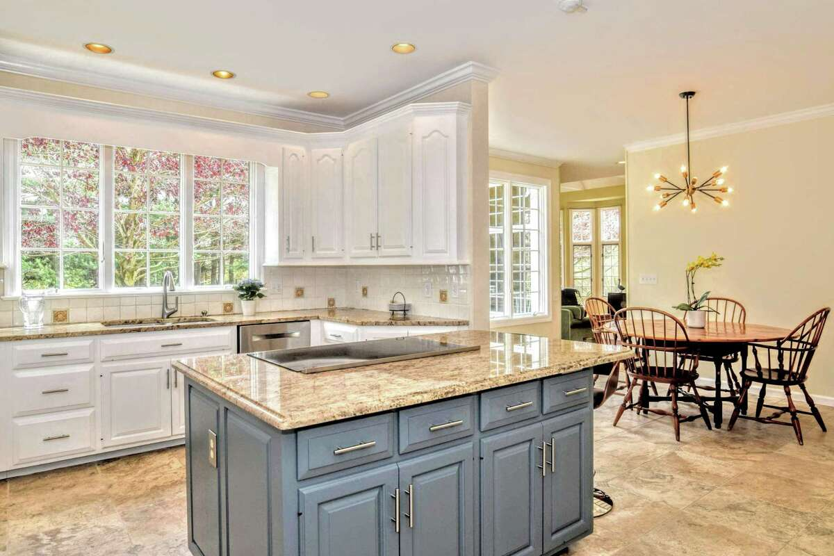 The gourmet eat-in kitchen has a center island/breakfast bar, granite counters, dry bar, pantry, ceramic tile backsplash, and eat-in area.