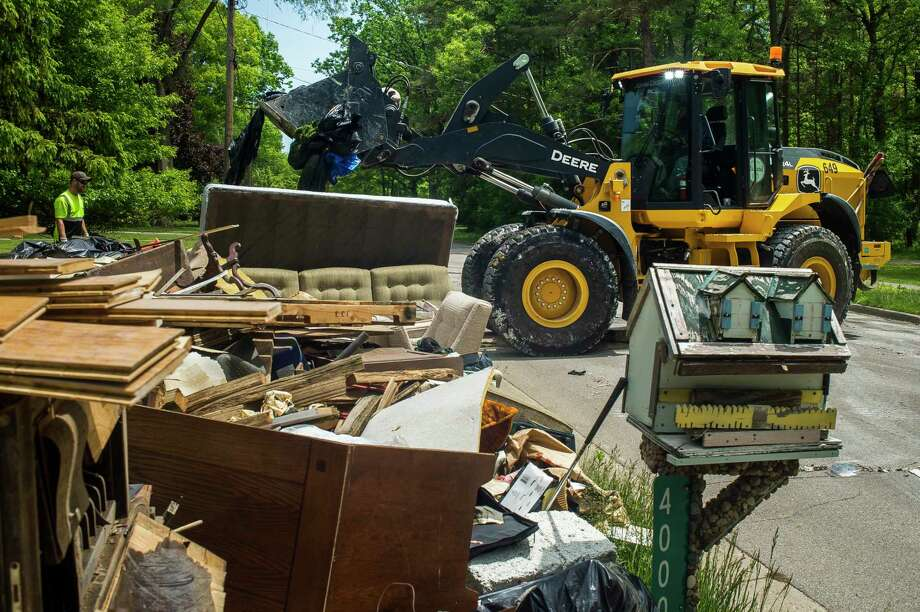 Clean up efforts after the flood continue on some of Midland's hardest hit streets Monday afternoon. City crews continue to make heavy item pickups to be delivered to the landfill. For more photos, visit www.ourmidland.com. (Katy Kildee/kkildee@mdn.net)