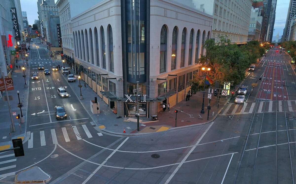 A few cars turn from Stockton Street past a very empty Market Street as curfew takes hold in San Francisco, Calif., on Sunday, May 31, 2020. Mayor London Breed issued a curfew following several nights of violent protests and looting in the city.