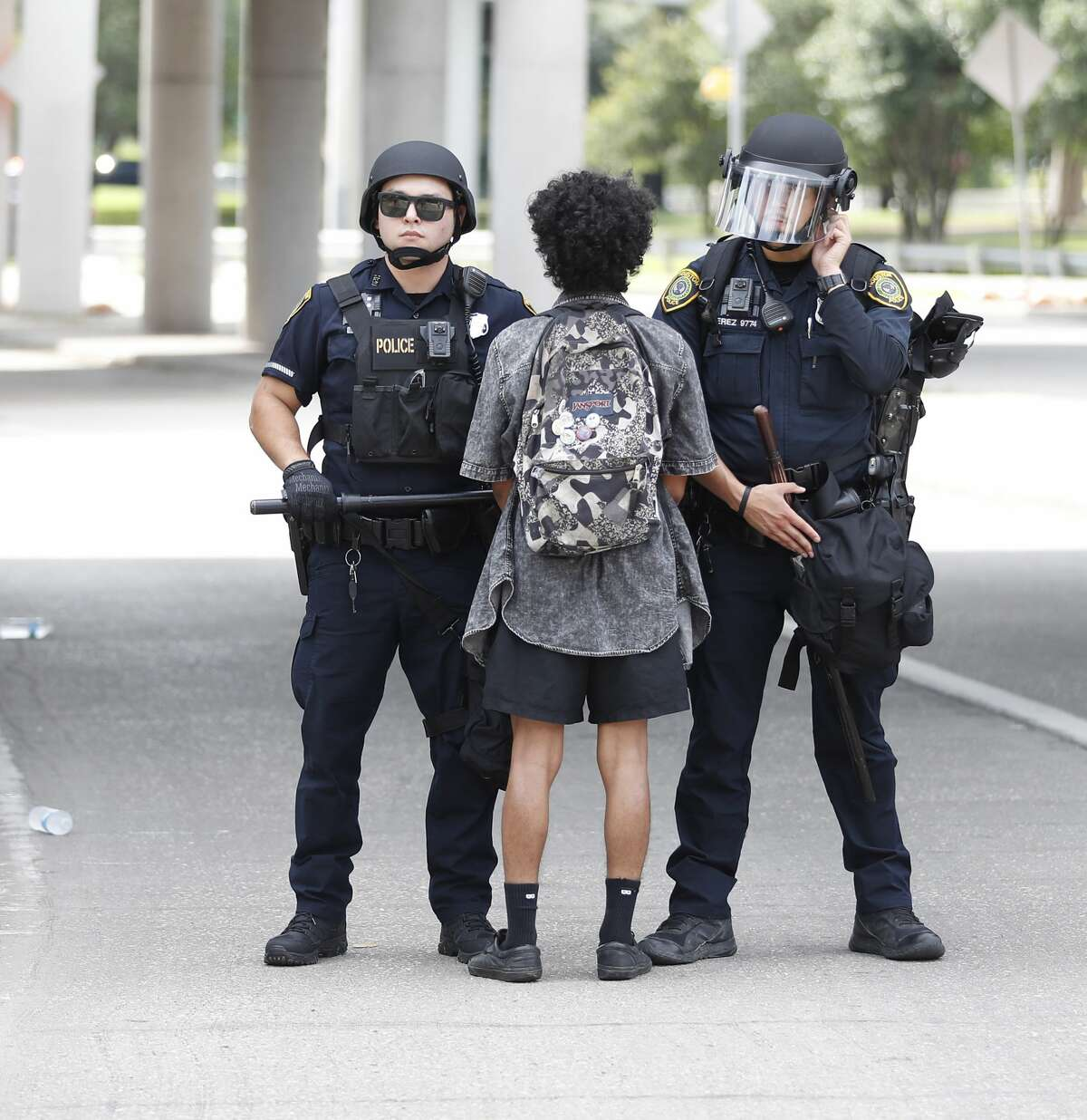 A protester is stopped by Houston Police officers, under I-45 on Allen Parkway as Black Lives Matter Houston protesters marched for George Floyd, in Houston, Friday, May 29, 2020.