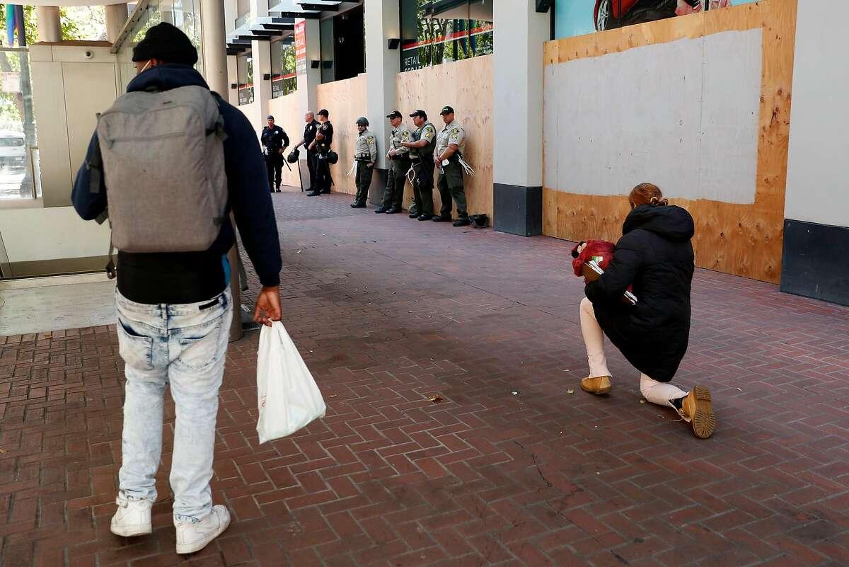 Maria Perez takes a knee near a group of Santa Barbara County Sheriff's Police on Market Street in San Francisco, Calif., on Monday, June 1, 2020.