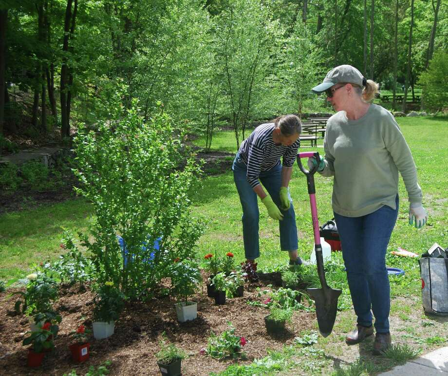 Heidi Riggs, left, and Sherry Johnson plant sun and shade gardens at the Chess Park in Wilton Center. Photo: Charles Johnson / Contributed Photo / Wilton Bulletin Contributed