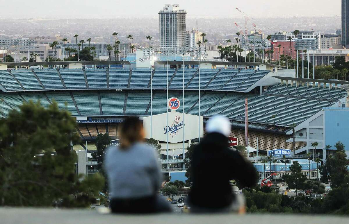 People sit on a hill overlooking Dodger Stadium on what was supposed to be Major League Baseball's opening day March 26. This might be as close as fans get to any action if owners and players can hammer out an agreement for a 2020 season.