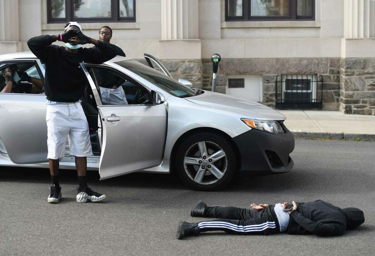 A group of protesters re-enact the death of George Floyd during the Black Lives Matter protest in front of the Public Safety Complex in Greenwich, Conn. Monday, June 1, 2020. More than 50 protesters gathered peacefully in honor of George Floyd and all other victims of police brutality, chanting their names and asking what the Greenwich Police Department is doing to avoid profiling, racism, and brutality within its system.