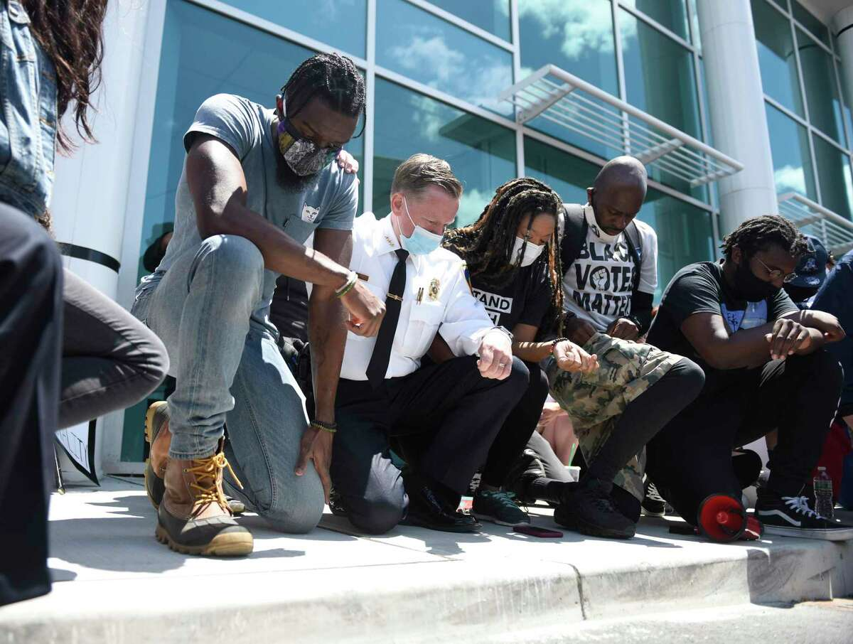 """Stamford Police Chief Tim Shaw, second from left, takes a knee with #JusticeForBrunch Black Lives Matter protest organizers outside the Stamford Police Department in Stamford, Conn. Sunday, May 31, 2020. About 500 people marched from Harbor Point to the Stamford Police Station in honor of George Floyd and all other victims of police brutality. Protestors also shouted the name of Steven Barrier, who died in Stamford Police custody in October of 2019. Stamford Police Chief Tim Shaw spoke at the event saying """"This police department is not silent. We are disgusted as well,"""" before taking a knee with protestors for a moment of silence."""